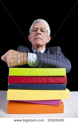 Senior teacher portrait behind some books (isolated on black)