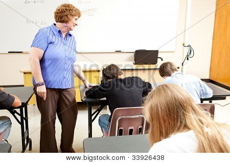 Teacher observes her high school class as they are taking a test.
