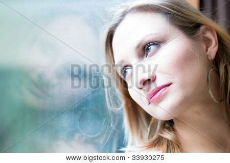 Beautiful woman standing by a window looking outside