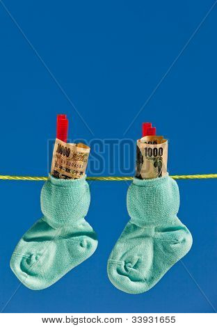 baby socks on clothesline with yen banknotes from japan.