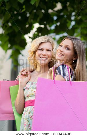 Two Female Friends Smiling With Shopping Bags