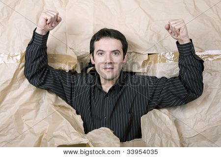 young man making a large hole in a paper