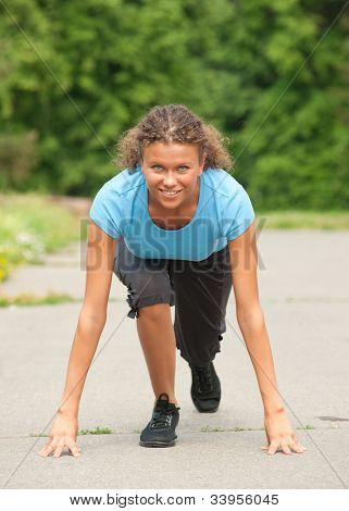 Young athletic woman in start position on track outdoors