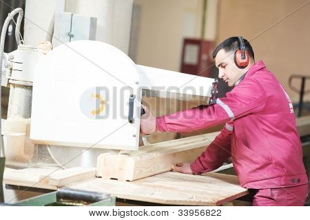 Closeup process of carpenter worker with circular saw machine at wood beam cross cutting during furniture manufacture