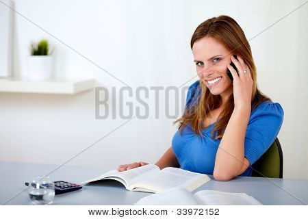 Pretty Young Girl Speaking And Browsing A Book