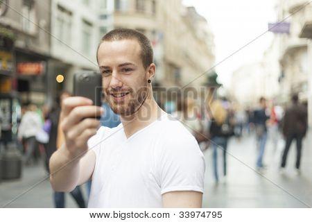 Männer auf der Straße Fotografieren mit Handy, Hintergrund ist verwaschenes Stadt