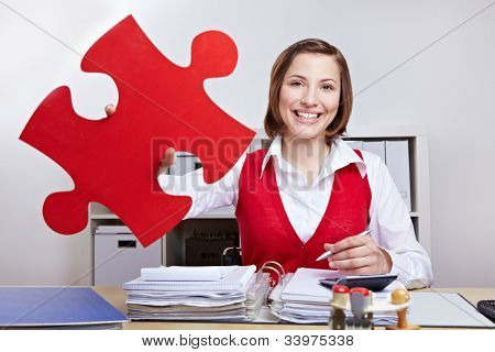 Attractive businesswoman holding oversized red jigsaw puzzle piece