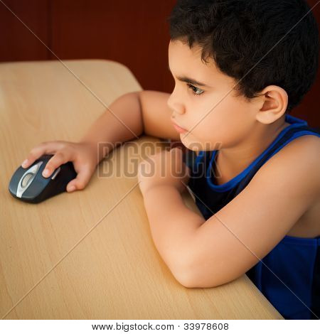 Cute hispanic boy working with a computer on his bedroom at night