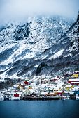 wooden houses on the banks of the Norwegian fjord, beautiful mountain landscape in winter poster