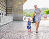 Mother And Baby Walking In City