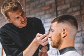 Young Male Barber Cutting Clients Hair With Scissors. Young Bearded Man Getting Haircut By Hairdress poster