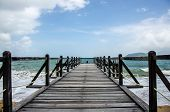 Old Wooden Pier By The Sea. A Pier With Wooden Railing, A Rope Is Stretched Along The Railing. White poster