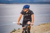 Young Guy Riding A Mountain Bike On A Bicycle Route In Spain. Athlete On A Mountain Bike Rides Off-r poster