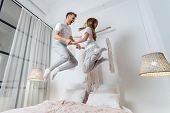 Happy And Smiling Young Adult Woman Holding Hands With Man, Spending Morning At Home, Jumping Up On  poster