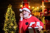 Christmas. New Year Holidays. Winter. Happiness. Presents. Bearded Man In Santa Hat Holds Christmas  poster