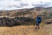 Hiker With Backpack Looking At Landmannalaugar Valley. Iceland. Colorful Mountains On The Laugavegur poster