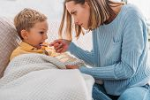 Attentive Mother Giving Medicine To Diseased Son Wrapped In Blanket poster