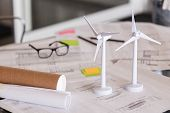 Close up of wind turbines on a table with architectural plan blueprints. Two models of wind turbines poster