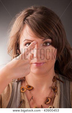 Постер, плакат: Женщина делает EFT на конце брови точки Эмоциональная Свобода Техника выстукивать форма counse, холст на подрамнике