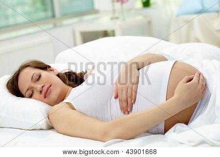 Joven embarazada dormir tranquilamente en la cama