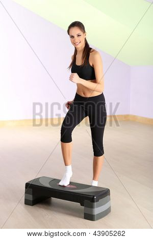 Young woman doing fitness exercises on stepper at gymnasium
