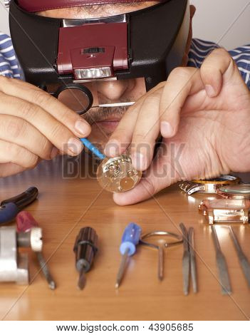 Watch repair craftsman repairing watch. Focus on face watchmaker