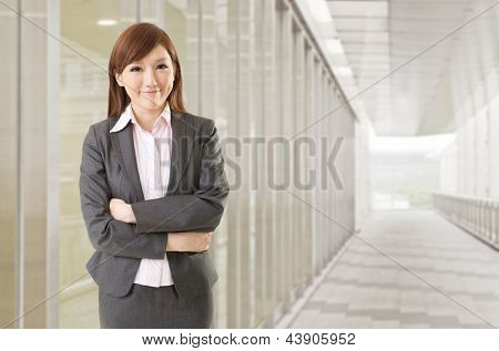 Confident Asian business woman stand in front of office buildings.