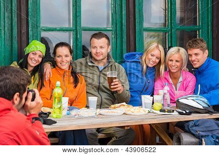 Young man taking picture of smiling friends during weekend