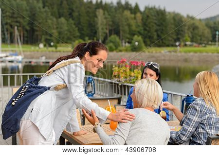 Woman arriving at outdoor restaurant terrace to her girl friends