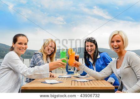 Mujeres alegres tostado con un cóctel en la terraza de verano del restaurante al aire libre