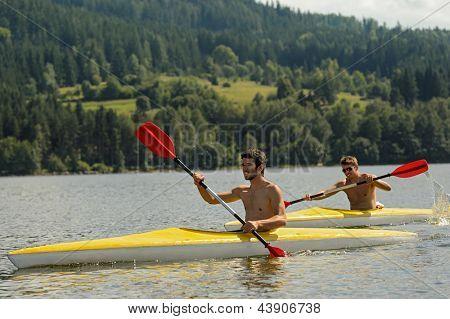 Young men kayaking summertime vacation on river paddling