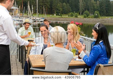 Surprised birthday girl receiving dessert from friends at terrace restaurant