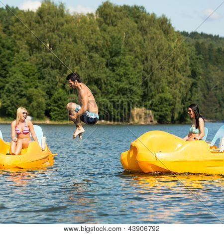 Young friends having fun jumping into water from pedal boats