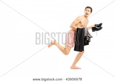 An embarrassed naked man in underwear holding his clothes and running, isolated on white background