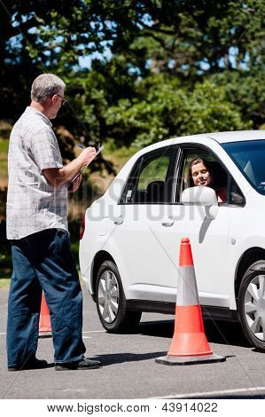 Learner driver girl with instructor taking lessons