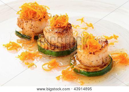 Fried sea scallops with orange zest in plate