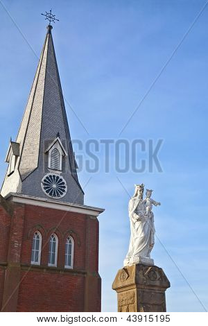 Statue of the Virgin Mary holding the baby Jesus with a church steeple in the background.
