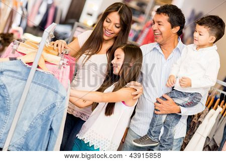Family shopping for clothes and looking happy