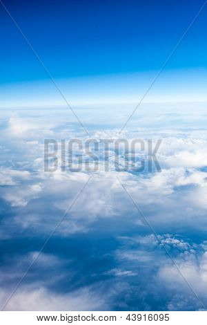 clouds. top view from the window of an airplane flying in the clouds. clear blue sky under high clouds located