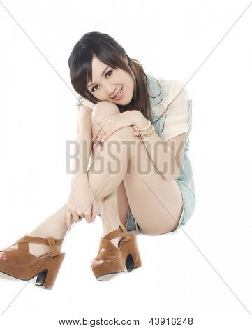 Beauty girl sits on a floor and looking at the camera