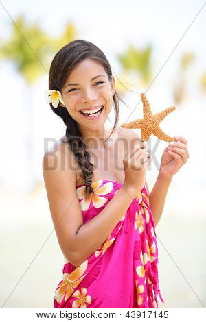 Summer vacation woman smiling happy holding starfish on Hawaiian beach. Cute multicultural Asian Caucasian female model joyful and adorable in red pink sarong
