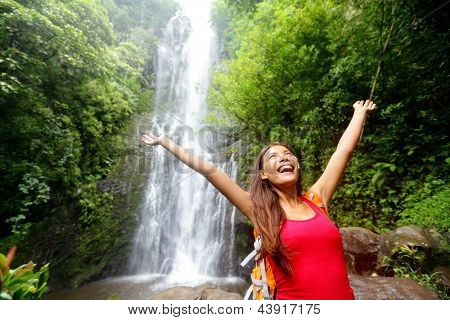 Hawaii woman tourist excited by waterfall during travel on the famous road to Hana on Maui, Hawaii. Ecotourism concept image with happy backpacking girl. Mixed race Asian / Caucasian backpacker.