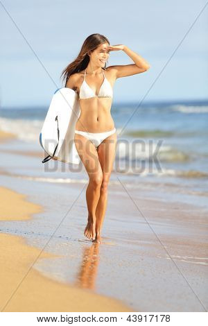 Beach fun woman surfing with bodyboard on summer vacation holidays travel. Beautiful hot girl in bikini looking at the sea. Multicultural Asian / Caucasian female model. Kaanapali beach, Maui, Hawaii.