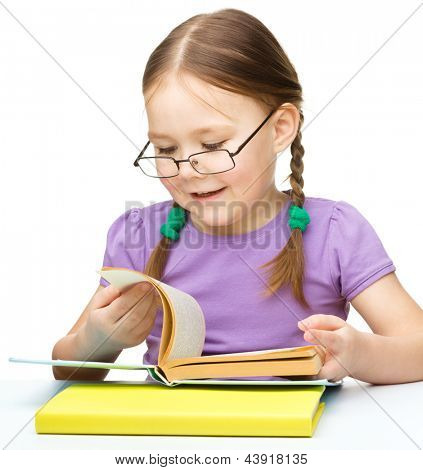 Niña linda está leyendo un libro mientras se está usando gafas, aislados en blanco