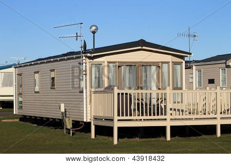 Scenic view of trailers in caravan park with blue sky background.