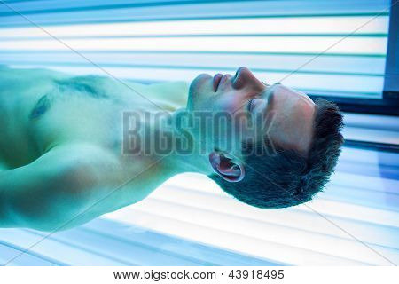 Handsome young man relaxing during a tanning session in a modern solarium