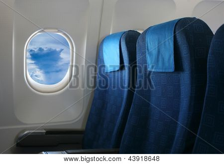 Airplane seat and window inside an aircraft with view of cumulus cloud