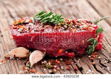 Raw beef steak on a dark wooden table.