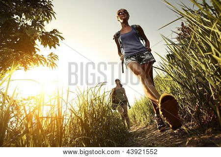 Two young ladies with backpacks walking through green tropical meadow