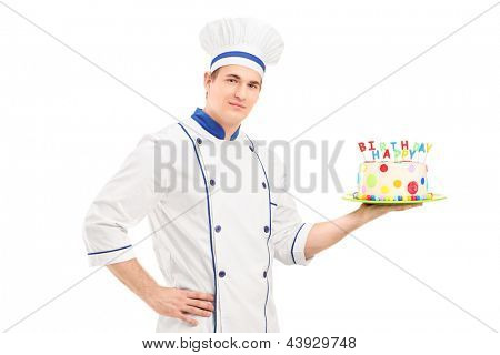 Young male chef in a uniform holding a decorated birthday cake isolated on white background